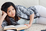 Woman lying on the floor while holding a book