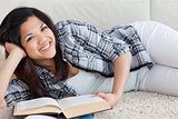 Woman smiling and holding a book as she lies on the floor