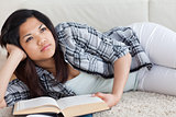 Thinking woman lying on the floor while holding a book