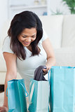 Smiling woman holding clothes from a shopping bag