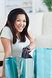 Smiling woman taking clothes off from a shopping bag