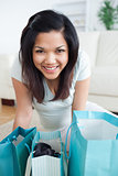 Smiling woman standing over shopping bags