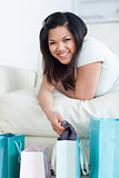 Woman on a couch holding clothes up from a shopping bag