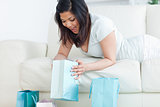 Surprised woman on a couch looking in a shopping bag