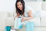 Woman holding up a shopping bag while lying on a sofa