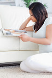 Woman reading a magazine as she sits beside a couch