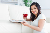 Woman on her knees holding a glass of red wine and a magazine