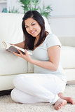 Woman holding a book while sitting in front of a couch