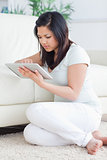 Woman holding a tactile tablet in front of a couch