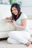Smiling woman holding a tactile tablet in front of a couch