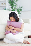 Sad woman holding a pillow