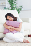 Woman looking sad while holding a pillow