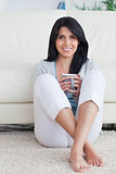 Woman holding a mug with two hands and crossing her legs while s