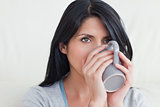 Woman drinking from a mug that she holds with two hands