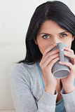 Close-up of a woman drinking from a mug that she holds with two 