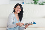 Smiling woman holding a magazine while leaning on a couch