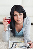 Woman lying on the floor while holding a glass of wine and a mag