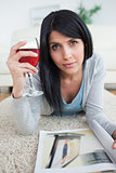 Woman with a magazine holding a glass of red wine