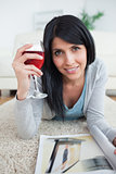 Woman smiling while holding a magazine and a glass of red wine