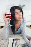 Woman thinking while holding a glass of red wine and a magazine