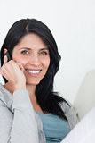 Smiling woman phoning while sitting on a sofa