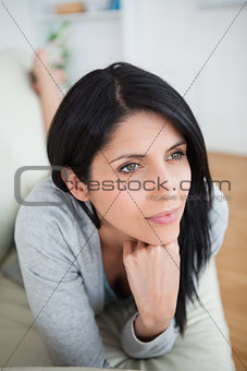 Woman holding her head with her fist as she lies on a couch