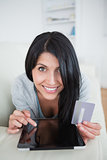 Woman smiling while holding a credit card and touching a tablet