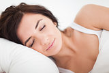 Peaceful brown-haired woman sleeping in the bed