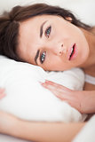 Brunette woman lying while placing her head on a pillow