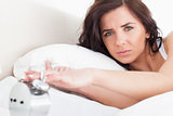 Serious woman switching off her alarm clock