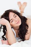 Peaceful woman closing her eyes while lying on her bed