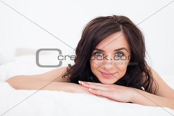 Calm brunette woman lying while smiling