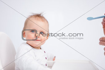 Smiling baby looking at the camera while being fed