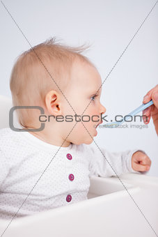Beautiful little girl being fed with a spoon