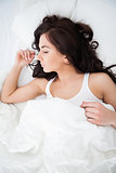 Brunette woman napping while lying under her quilt