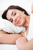 Peaceful woman waking up while lying in her bed