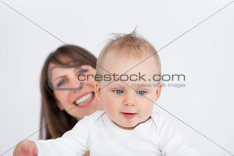 Smiling brunette woman holding her cute baby