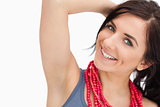 Smiling blue eyed woman posing with a red bead necklace