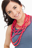Blue eyed brunette posing with a red bead necklace
