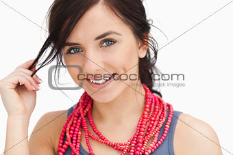 Smiling blue eyed woman with a red bead necklace