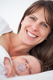Smiling brunette woman lying while her baby is sleeping