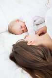 Brunette woman lying with her baby on her bed