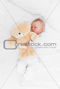 Baby sleeping while holding a teddy bear