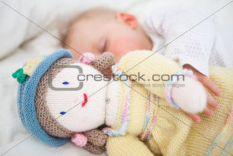 Baby sleeping while holding a plush doll