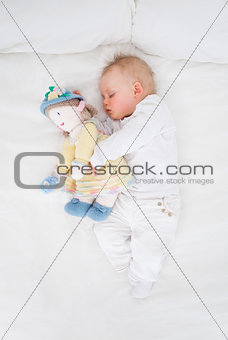 Baby sleeping while embracing a plush doll