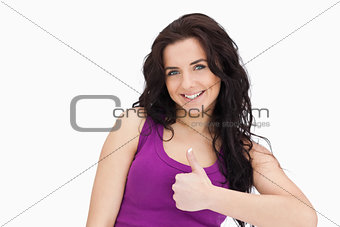 Smiling brunette the thumb-up