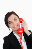 Happy woman in suit using a red dial telephone while looking up