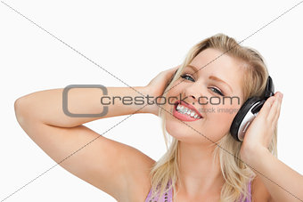 Blonde woman raising her arms while listening to music