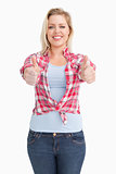 Happy blonde woman showing her two thumbs up