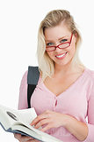 Happy young woman wearing glasses while holding a novel